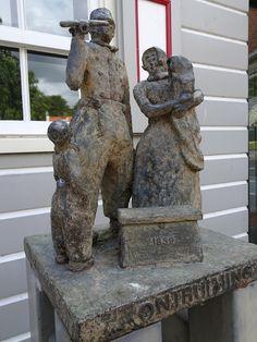 Schokland - Noordoostpolder. Ontruiming van Schokland 1859. Bronzen beeld van Piet Brouwer uit 1994. Het beeldje staat op een stalen sokkel voor het gerestaureerde 'Schokker huisje'. Afbeelding van een gezin in Schokker klederdracht. De man draagt een anker en een koffer staat voor hen. Foto: G.J. Koppenaal - 6/6/2016.  1994