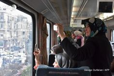 Syrian women take pictures as they ride a train travelling through Aleppo's devastated eastern districts for the first time in more than four years, on January 25, 2017. It is the train's first such...