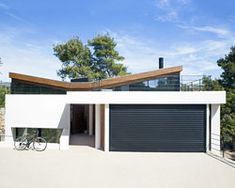 butterfly-roof 'wedge house' by schema is located in a piny area in greece