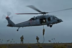 Explosive Ordnance Disposal sailors from the United States, Australia, and Canada fast rope out of a U.S. Navy MH-60S Nighthawk helicopter from Helicopter Sea Combat Squadron (HSC) 4 at Marine Corps Base Hawaii Kaneohe Bay on July 16, 2012, during RIMPAC 2012, the  world's largest international maritime exercise.