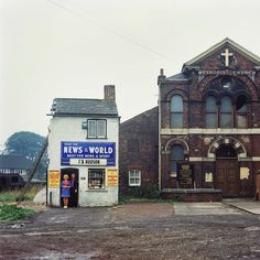 Mr and Mrs Hudson in Seacroft Green, Leeds. I took this photograph on the 14 August 1974 at about 11am. I like the way the ladder is propping up the shop. They had just moved into a new shop on the same spot, with the church getting a facelift to match