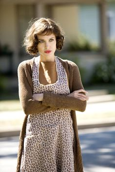 """1930s style-- Angelina Jolie on the movie """"Changeling"""". Long brown sweater and floral feedsack apron over her dress."""