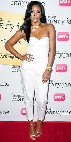 GABRIELLE UNION in a summery white jumpsuit with a sweetheart neckline, plus metallic ankle-strap Stuart Weitzman sandals