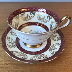 Royal Albert Vintage Teacup and Saucer Un-Named Pattern This is a beautiful regal china teacup and saucer. This set is a pinkish red, cream and white with lots of gold overlay patterns. In the centres are pretty bouquets of different coloured flowers and leaves. The edges, handle and foot