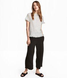 Musta. Pohjepituiset väljät housut pehmeää kangasta. Korkea joustovyötärö ja röyhelöreunaiset sivutaskut. Suora ja rento malli.