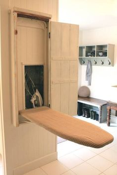Save space by building an ironing board cupboard right into the wall, and even build a small nook inside for your iron!