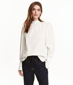 White. CONSCIOUS. Gently flared blouse in woven cotton fabric with a stand-up collar. Opening at back with buttons at back of neck. Long puff sleeves with