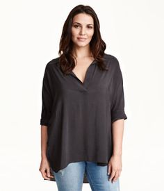 CONSCIOUS. V-neck blouse in sheer woven fabric. Long sleeves with button at cuffs. Slits at sides and slightly longer back section. Made partly from recycled polyester.