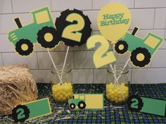 John Deere inspired centerpieces. Includes tractors, tractor tire, birthday numbers and balloon. Birthday decorations. Green and yellow.