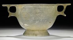 A GREEK PALE GREEN GLASS SKYPHOS   HELLENISTIC PERIOD, CIRCA LATE 2ND-EARLY 1ST CENTURY B.C.   The hemispherical body on tall ring foot, with lathe-cut concentric band on the underside, a single groove on the interior below the rim, the ring handles with horizontal upper and curved lower plates, the upper plates merging with the rim  3 1/8 in. (8 cm.) high