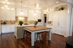 White cabinets, green island, sand glass backsplash by Siena Custom Builders