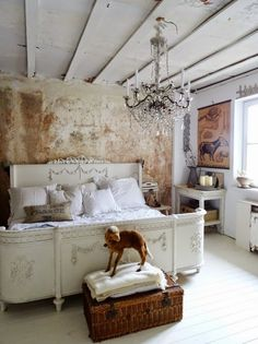White vintage carved wooden bed, white painted wood floor, and a chandelier. #shabbychic