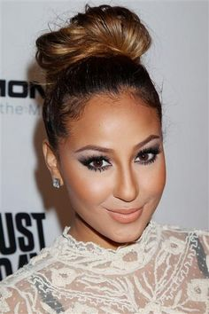 Up close a better Updo for and on Adrienne Bailon. I would like to see her try a bun that matches her hair color and a little more fullness but middle parts normally look best on Adrienne Bailon. xoxo Kriss