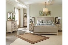 """The Demarlos Night Table from Ashley Furniture HomeStore (AFHS.com). With the rustic beauty of the gently distressed parchment white finish perfectly highlighting the elegant look of the shaped fronts and framed pilaster mouldings, the """"Demarlos"""" bedroom collection features large scaled headboard frames surrounding the nicely crowned textured upholstered cushion with bands and nail accent to complete the Vintage Casual look."""