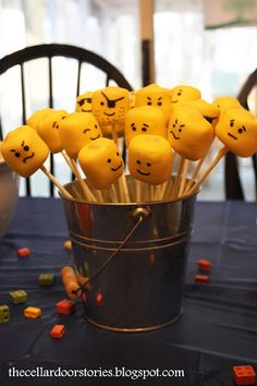 Lego Head Marshmallow Pops! Marshmallows with M stuck on top, dipped in melted yellow candy then faces drawn on