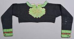 Spedetröja i blåsvart ullgarn garnerad med band och broderier kring halsringning, på bröstet och vid nederdelen på ärmen.   Tröjan är slätstickad med mönsterstickning.  Gröna sidenband (30 mm breda) runt halsringning, på bröstet och nederdelen på ärmen. Bröstet är dekorerat med broderier i rödrosa, vitt och orange i plattsöm, stjälksöm och kråkspark/gles flätsöm ovanpå de gröna banden.   Sydöstra Skåne
