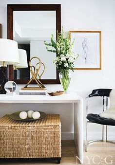An Italian Nero Portoro marble lamp and other decorative accessories sit on a vintage Milo Baughman console in the entry.