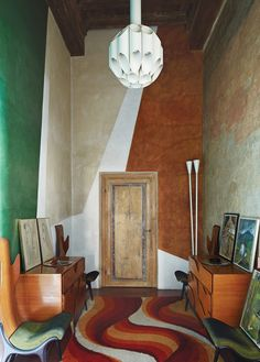 In the entry, Gio Ponti chairs and chests from the 1950s. The abstract wall paintings throughout the house were done by an artist friend. The house is a series of 13th- to 16th-century buildings that Baciocchi combined.