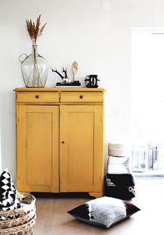 Holzschrank & Highboard in curry mit Vase und weiteren Accessoires in schwarz/weiss