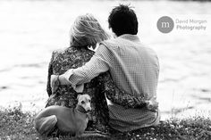 Young couple sitting by the lake with their little dog.