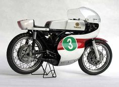 YAMAHA RD56 Motorcycle: Yamaha RD 56 Manufacturer: Yamaha Motor Co. Ltd., Iwata Type: Racing Year: 1965 Engine: Yamaha two-cylinder, two-stroke, with rotating-disk distribution. Displacement 249.7 cc. (56 mm. x 50.7 mm.) Cooling: Air Transmission: Seven-speed block Power: 47 h.p. at 13,000 r.p.m. Maximum speed: Over 140 m.p.h. Chassis: Double cradle, continuous, tubular. Front and rear, telescopic suspension Brakes: Front, central drum, four shoes; rear, central drum