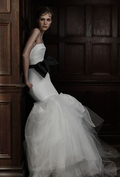 A strapless @verawanggang wedding dress with a tulle mermaid skirt and a black bow | Brides.com