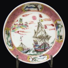 An Early 18th Century Chinese Export Porcelain Saucer, Yongzheng c.1730. Decorated in Rose-Verte Enamels Depicting a Three Mast European Sailing Ship Next to a Smaller Chinese Vessel with a Chinese Walled Town in the Background.   References : For an 18th century Chinese porcelain plate with this pattern see : The Choice of the Private Trader, The Private Market in Chinese Export Porcelain illustrated from the Hodroff Collection (David Zwemmer,1994. ISBN 0 302 00642 7).