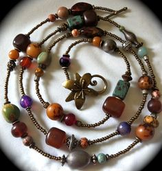 Long beaded necklace with amethyst, antiqued brass, sterling,turquoise, and rare vintage beads.