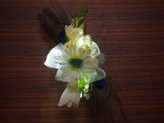 Glow in the dark custom prom corsage that lights up with an on/off switch in shades of white, royal blue, green and yellow with diamonds, glitter, lily of the valley, gerber daisy, freesia, and Peacock feather on silver cuff with matching boutonnière. www.urbanelementsinteriorspace.com in Portland, OR.