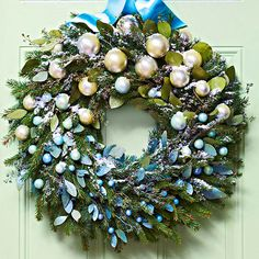 Take an evergreen wreath from plain to showstopping with only a few additions. First, wire seeded eucalyptus sprigs and silver glass balls in various sizes to floral picks. This step will make the sprigs and glass balls easier to arrange in the wreath, but they can also be wired on directly if desired. Next, spray half of the eucalyptus blue and the other half chartreuse; let dry. Using spray paint in the same colors, mist the glass balls with a mix of the two colors as shown. Create an…