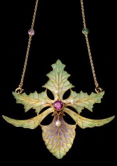 An Art Nouveau gold, plique-à-jour enamel, pearl and ruby pendant, by Georges Fouquet, circa 1898. The pendant designed as an orchid decorated with plique-à-jour enamel, centring a round faceted ruby, surrounded by four small pearls set to the anthers, mounted in yellow gold, suspended from a gold chain set with gems. Collection of Mikimoto Pearl Museum. #Fouquet #ArtNouveau #pendant