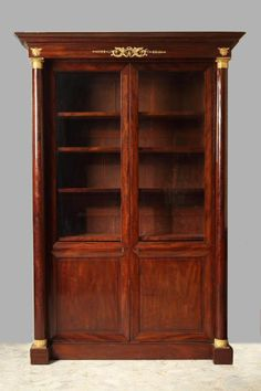 Large mahogany bookcase with molding, mahogany veneer, and gilt bronze accents. Two columns set in the front of the case are capped with gilt bronze rings sculpted with water leaves and...
