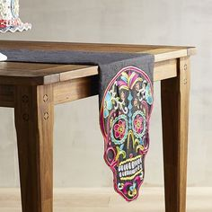 Too pretty to be scary: A brightly colored Day of the Dead skull adds to the elegance of our black table runner.