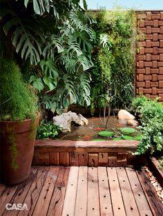"""A fonte intensifica o frescor, atrai pássaros e tem o poder de tranquilizar. """"Seu som precisa ser suave e equilibrado como uma chuva fina"""", ensina o paisagista Odilon Claro que reproduziu o efeito com esta graciosa fonte de cobre. Desenhada por ele, a peça lembra folhas secas e surge sobre o espelho-d'água com carpas e Nymphaea. Nas paredes, pendem Monstera deliciosa, Columnea microphylla, Asparagus densiflorus e Rhipsalis baccifera."""