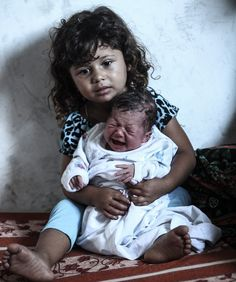 A little girl holds her new sister who was born in a UN school in Gaza at the…