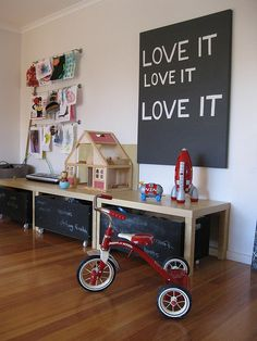 a place for kids to play and learn...storage bins on wheels  painted with chalk board paint and hanging rods for art work - super fun and practical!