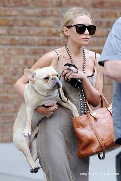 Ashley Olsen with her perfect pair of Arm Candy! This poor dog!!  He is welcomed to my house any time!