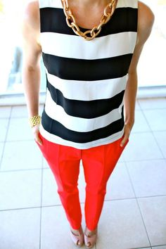 Bold statement: black and white thick-stripe shirt, colored pants, and chunky gold chain necklace.