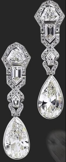 A pair of Art Deco diamond earrings, circa 1920.   Each formed as an articulated geometrically designed fancy and single-cut diamond-set surmount suspending a pear-cut diamond, one weighing 5.01 carats, the other weighing 5.03 carats, mounted in platinum, the remaining diamonds estimated to weigh approximately 6.19 carats in total, length 4.6cm.
