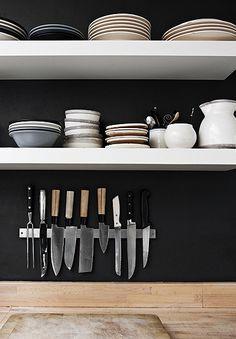 sfeerimpressie keuken met donkere achtergrond, witte planken en houten blad