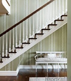The entry's hand-blocked wallpaper is Claremont's Palm Stripe.   - HouseBeautiful.com