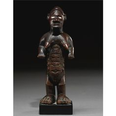 A FINE BEMBE FEMALE ANCESTOR FIGURE, REPUBLIC OF THE CONGO biteke, standing on enlarged domed feet, the female figure with protruding breasts and elaborate scarification on the abdomen, the hands cupped in an offering gesture, the elegant face with protruding jaw, porcelain inset eyes and a sunken C-shaped motif inside the coiffure; fine varied dark brown patina with traces of light pigment. height 6 1/2 in. 16.5 cm