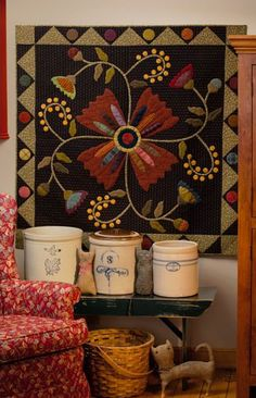 Lovely...Kim Diehl quilt pattern, displayed here as the backdrop for a collection of crocks & primitives.