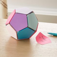 """A fun and colorful way to write memos! When you're searching for a co-worker or teacher gift, our Poppin Sticky Memo Ball has answers. It's a functional desktop memo center with a pad of sticky notes on each of its 12 sides. Use up all the notes to reveal a fun, office-friendly alternative to a magical 8-ball, with answers to such pressing questions as """"should the boss treat us to lunch this week"""" or """"do I deserve a huge promotion?"""""""