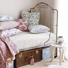love the iron headboard, comfy pillows and a basket for storage under the bed