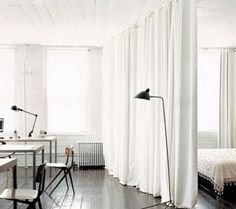 white curtains & bricks, friso kramer chairs, wood floor, simple lamps by serge mouille & jieldé