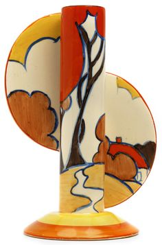 'Autumn' pattern, Fantasque, Bizarre, Finned Stamford Vase,1930, by Clarice Cliff. Slender cylindrical form with applied circular panels. Painted trees with sinuous trunks and large balloon shapes tops by bushes and a small cottage in a wood. 20cm high. Black printed Bizarre mark and moulded number 464.