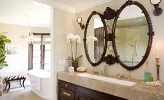 Ornate oval double black mirrors, chocolate brown bathroom cabinets and white porcelain tub with zebra bench!  gray beige paint wall colors.