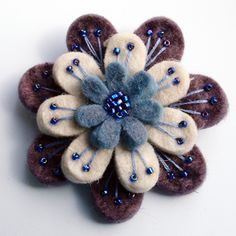 A beautiful, feminine brooch made from 3 layers of scrumptiously soft wool felt.Embroidered and beaded with metallic blue-violet seed beads, and firmly attached to a 1