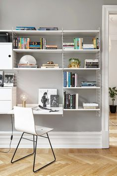 Workspace/study/office: white String shelving system, white chair, grey walls, herringbone floor, tall skirting boards, ornate cornices